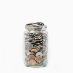 Isolated coins in jar on white