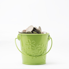 Isolated green bucket full with coins