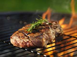 Aluminium Prints Grill / Barbecue steak with flames on grill with rosemary