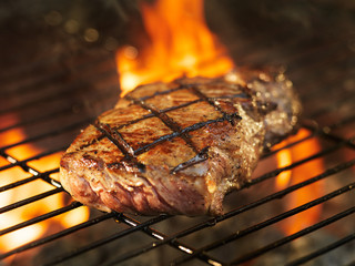 Foto op Plexiglas Steakhouse beef steak cooking over flaming grill