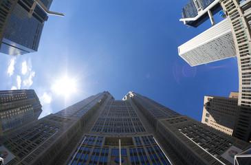 東京都庁と新宿高層ビル街を見上げる 太陽と快晴青空