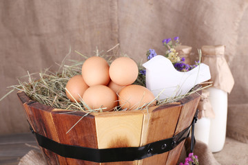 Big round basket with dried grass, milk and fresh eggs