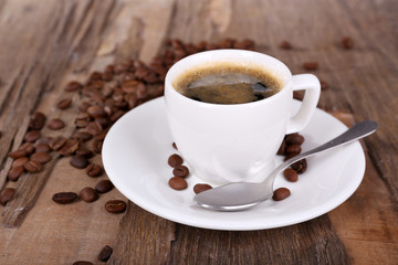 Cup of coffee and coffee beans on wooden background