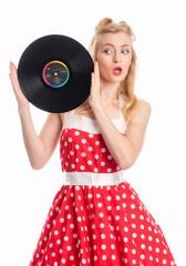 Erstaunte Frau hält eine Schallplatte