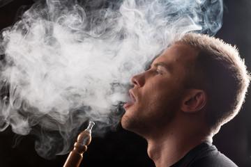 Close-up of man smoking traditional hookah pipe.