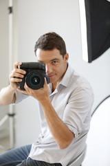 Photographer in studio with lighting equipment