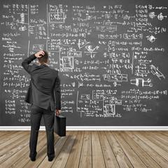Businessmann steht vor Tafel mit Formeln