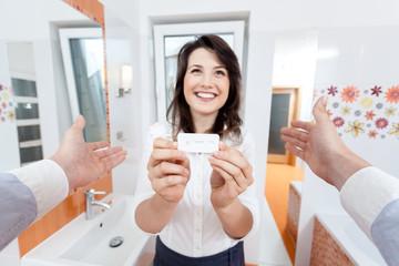 Woman showing positive pregnancy test