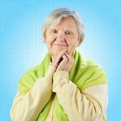 Senior happy woman looking to camera on blue background.