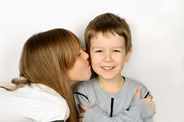 girl kissing little cheerful boy on light gray background. he fo
