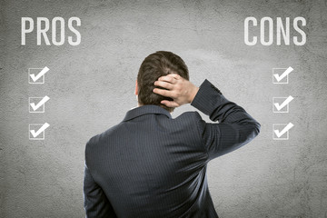 Businessman select all pros and cons in front of grey wall