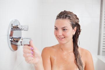 Beautiful young woman taking a shower/hot bath tub and washing hair