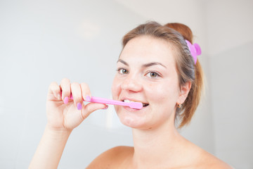 Beautiful/attractive young woman/girl cleaning her teeth/dental hygiene in bathroom