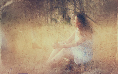 surreal blurred background of young woman sitting on the stone i