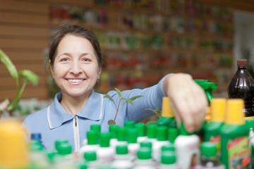 gardener chooses liquid fertilizer at  shop