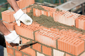 Construction mason worker with trowel during bricklaying works