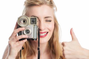 Frau mit Fotoapparat zeigt Daumen hoch