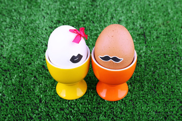 Pair of eggs in egg cups on green grass background