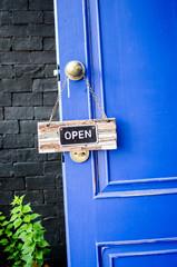 open label hanging on blue door in garden