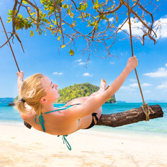 Lady swinging on the tropical beach