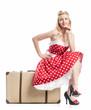 Eine Frau sitzt auf einem Koffer und wartet