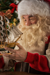 Santa Claus in his workshop making new toys