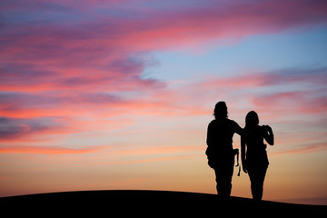 silhouetted couple watching sunset sky