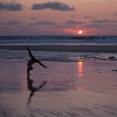Fototapete - silhouetted gymnast dong handstand on beach in sunset light