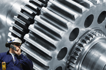 Wall Mural - engineer with large cogwheel and gears machinery