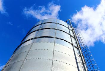 Towering grain silo under blue skies.