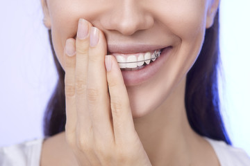 Portrait of Beautiful smiling girl covering her retainer for tee