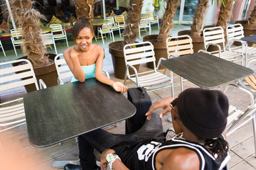 African man sitting with girlfriend holding hands in cafe