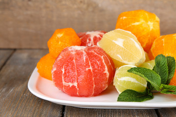 Citrus fruits without skin, on plate, on wooden background
