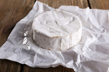 Camembert cheese on paper on wooden background