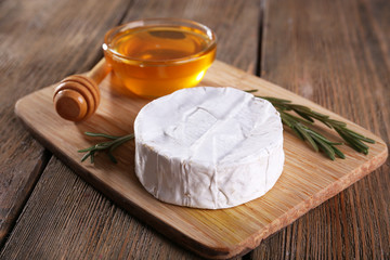 Camembert cheese and honey in glass bowl