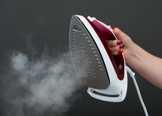 Woman holding an iron with steam