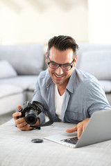 Man at home using digital camera and laptop