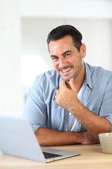 Mature man working at home with laptop