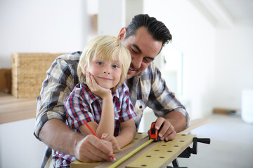 Father with kid measuring wood plank
