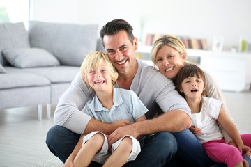 Portrait of happy family sitting on floor