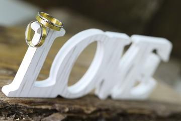 Trauringe auf Holz mit Schild Love