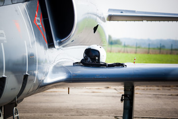 Detail of military fighter/interceptor/jetplane jet engine and wing with pilot's oxygen mask and helmet lying on, ready to take off in case of terrorist attack (colorful image)