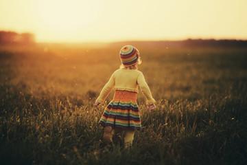 little girl runnig to the sunset