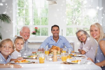 Composite image of family smiling at thanksgiving