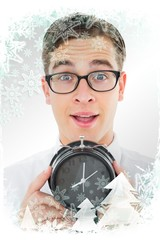Composite image of geeky businessman holding alarm clock