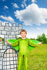 Boy in costume of green dragon near drawn tower