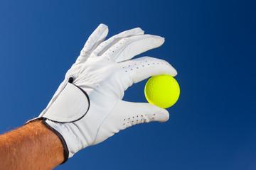 Foto op Plexiglas Golf Hand wearing golf glove holding a yellow golf ball