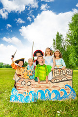 Group of kids in different costumes stand on ship