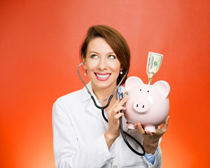doctor listening with stethoscope to piggy bank, red background