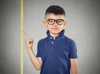 Child pointing at his height on measuring tape